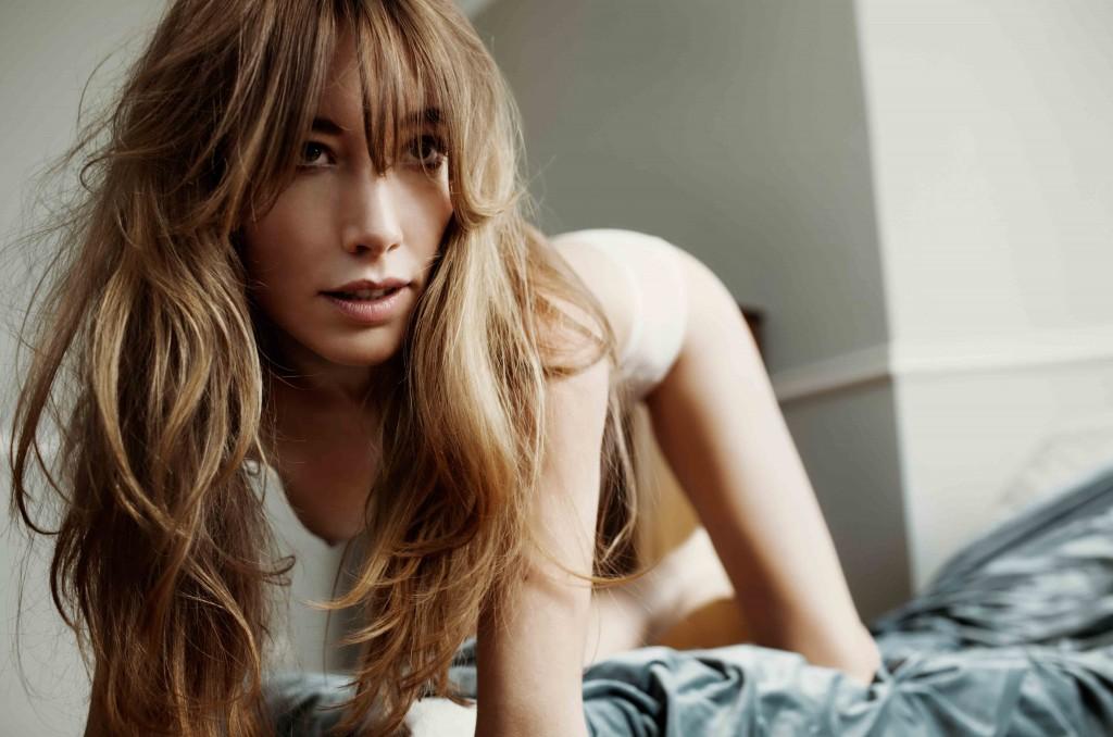 Nackte Frau kniet auf einem Bett