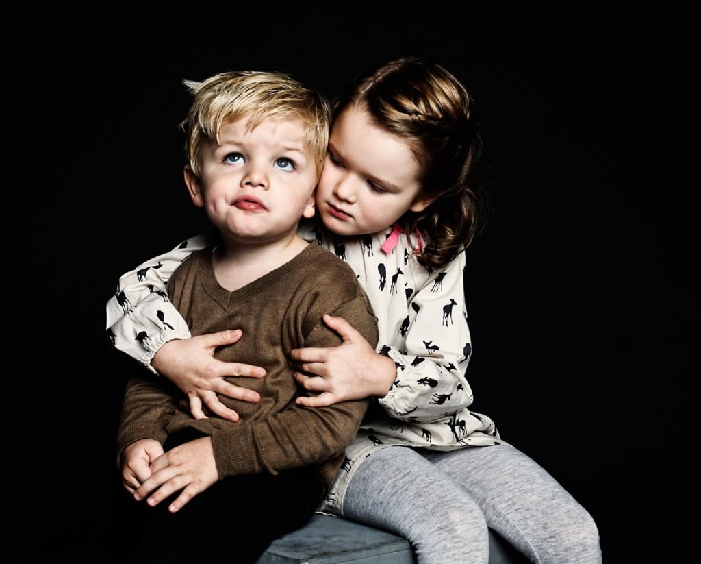 Aufnahme eines sich umarmenden Geschwisterpaares vor schwarzem Hintergrund
