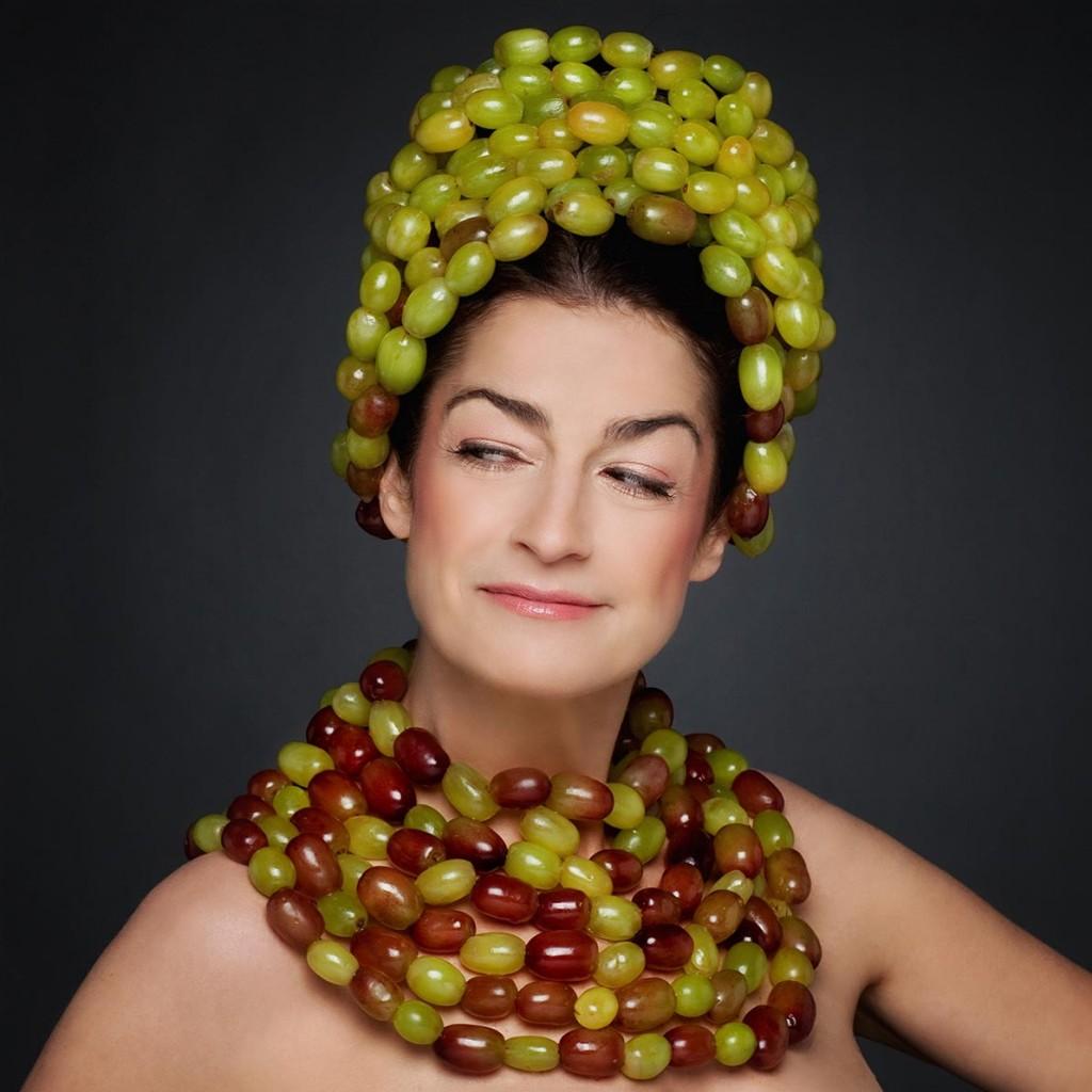 Portrait einer Frau mit Kopf- und Halsschmuck aus gelben und roten Tomaten