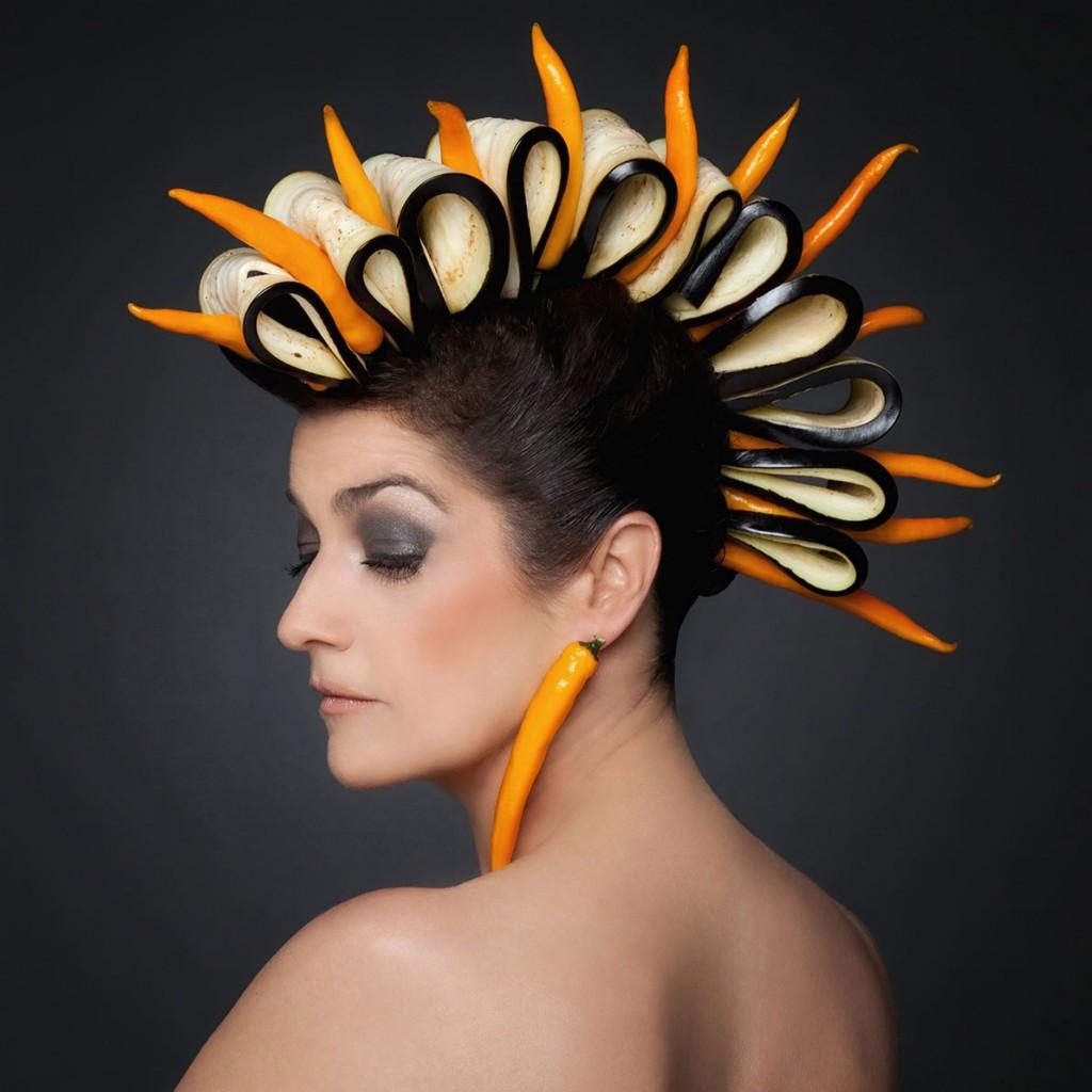 Portrait einer Frau mit Kopf- und Ohrschmuck aus Peperoni und Auberginen
