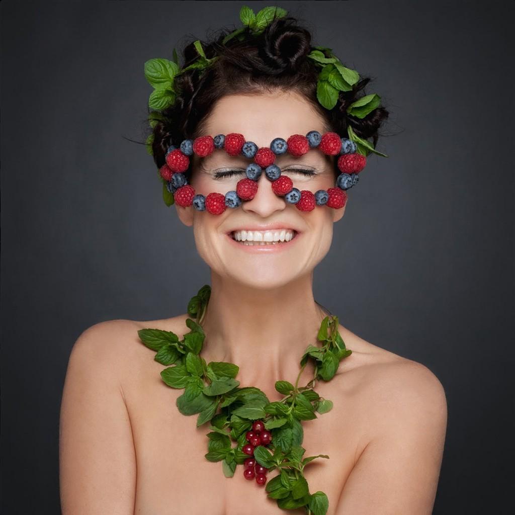 Portrait einer Frau mit Kopf- und Halsschmuck aus Minze und Waldbeeren